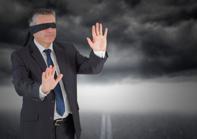 digitally composite image of businessman in blindfold against storm cloud